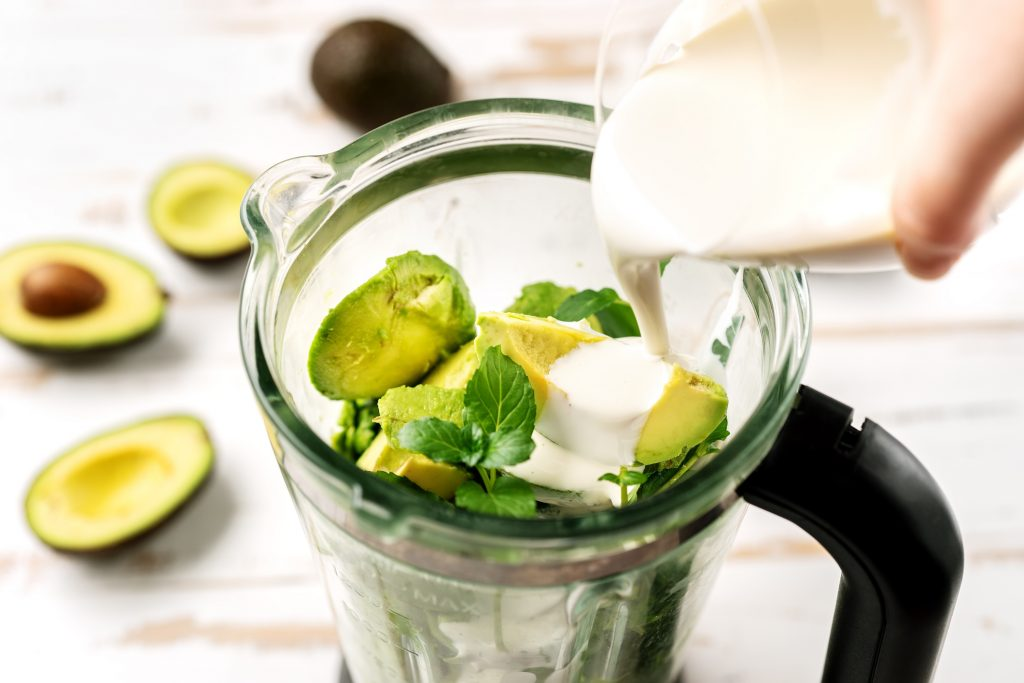 Pouring vegetarian cream into blender with avocados. Healthy ice cream preparation