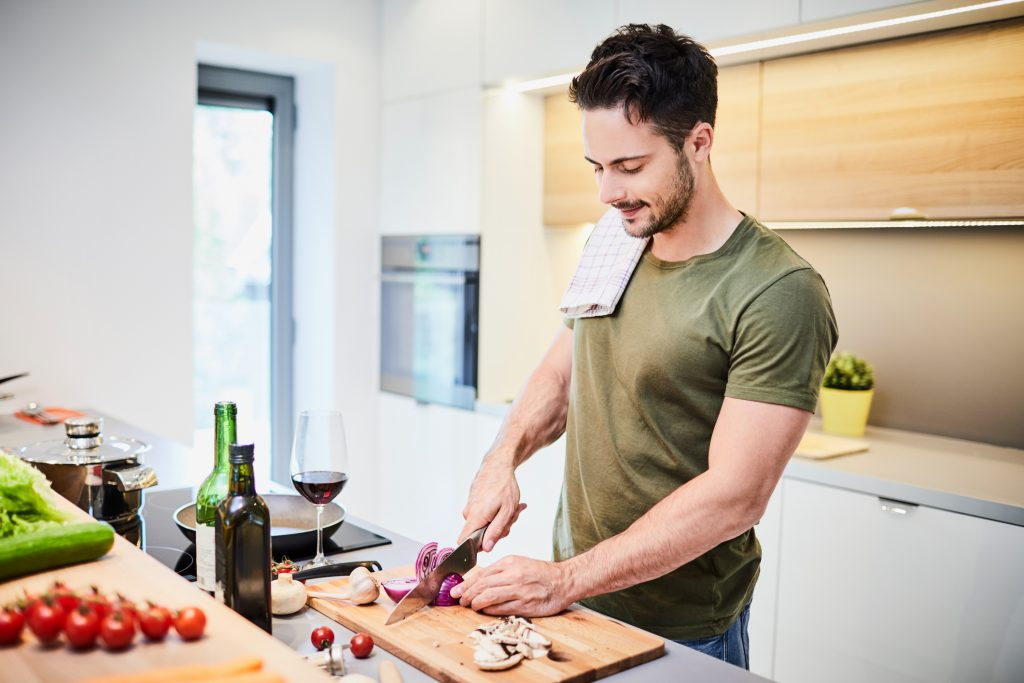 Handsome young man preparing helathy dinner, standing in the kichen and cutting vegetables